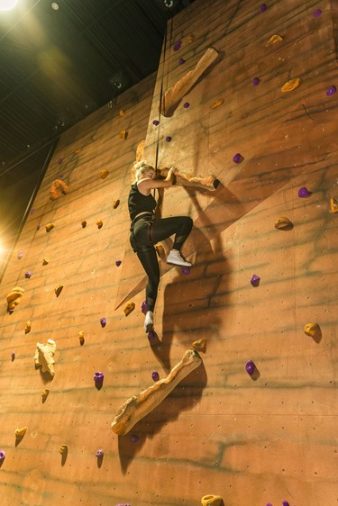 Woman scales indoor climbing wall at The Bear Grylls Adventure