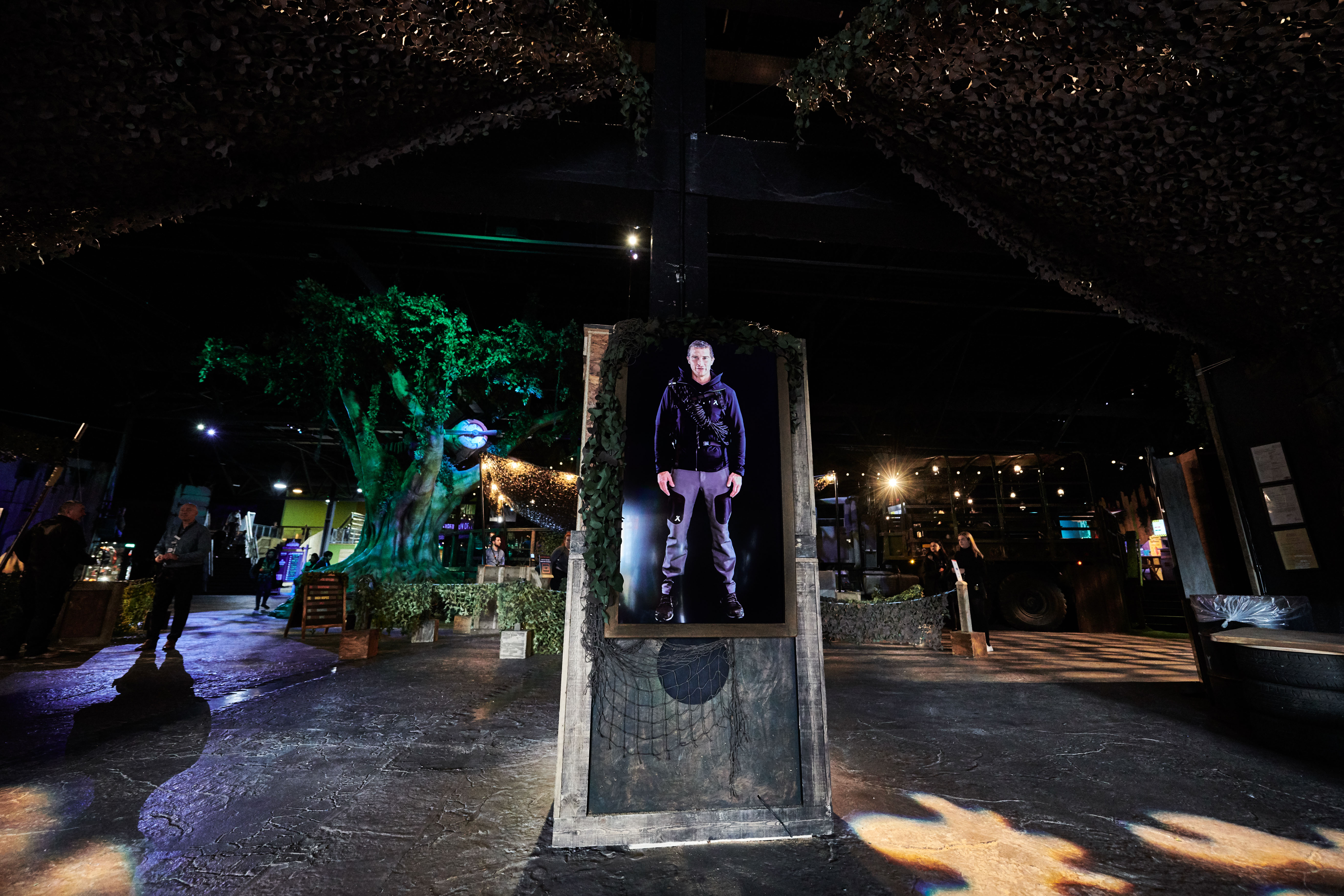 Bear Grylls welcomes guest on a screen in The Bear Grylls Adventure main entrance