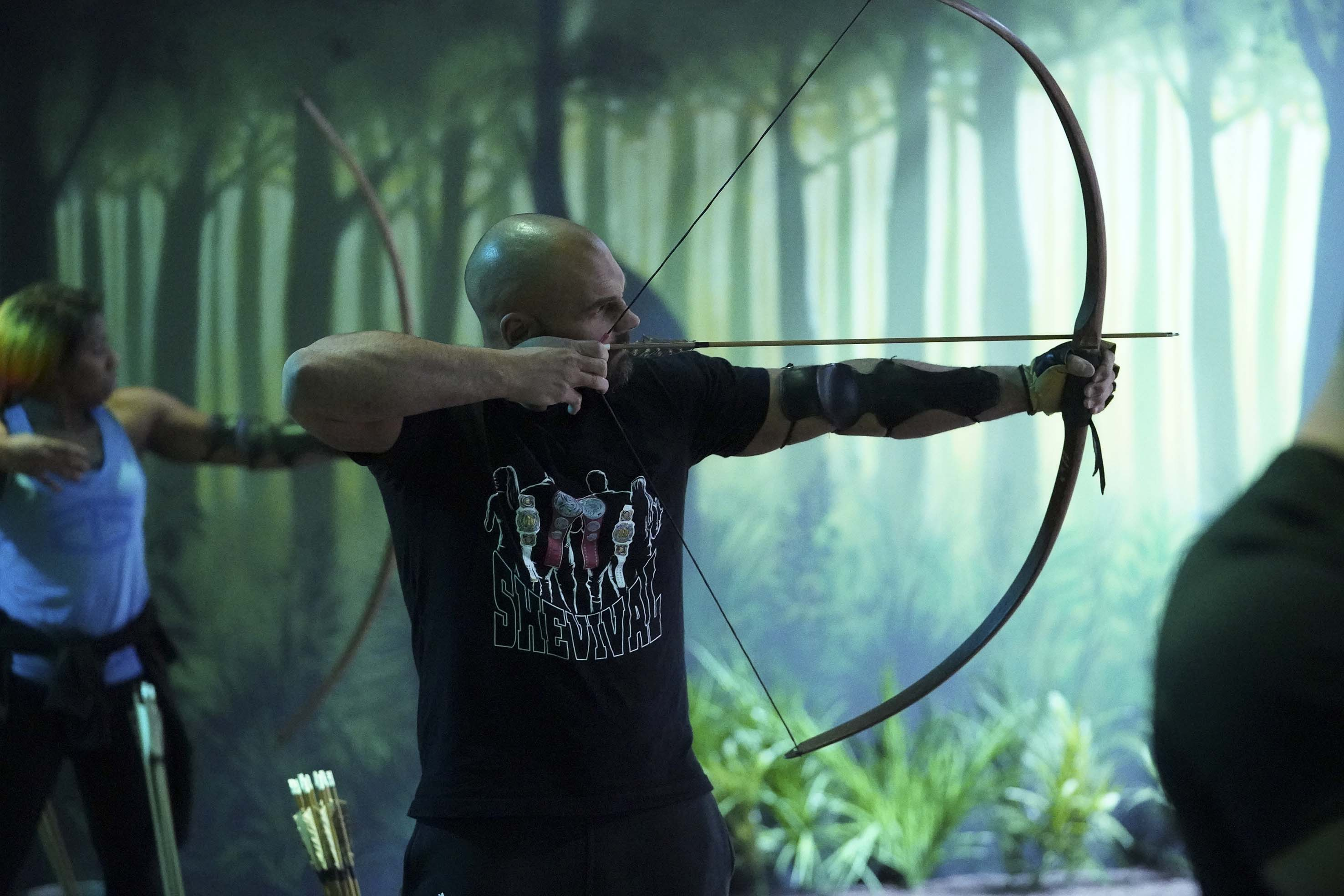 Man takes aim at target on archery range at The Bear Grylls Adventure